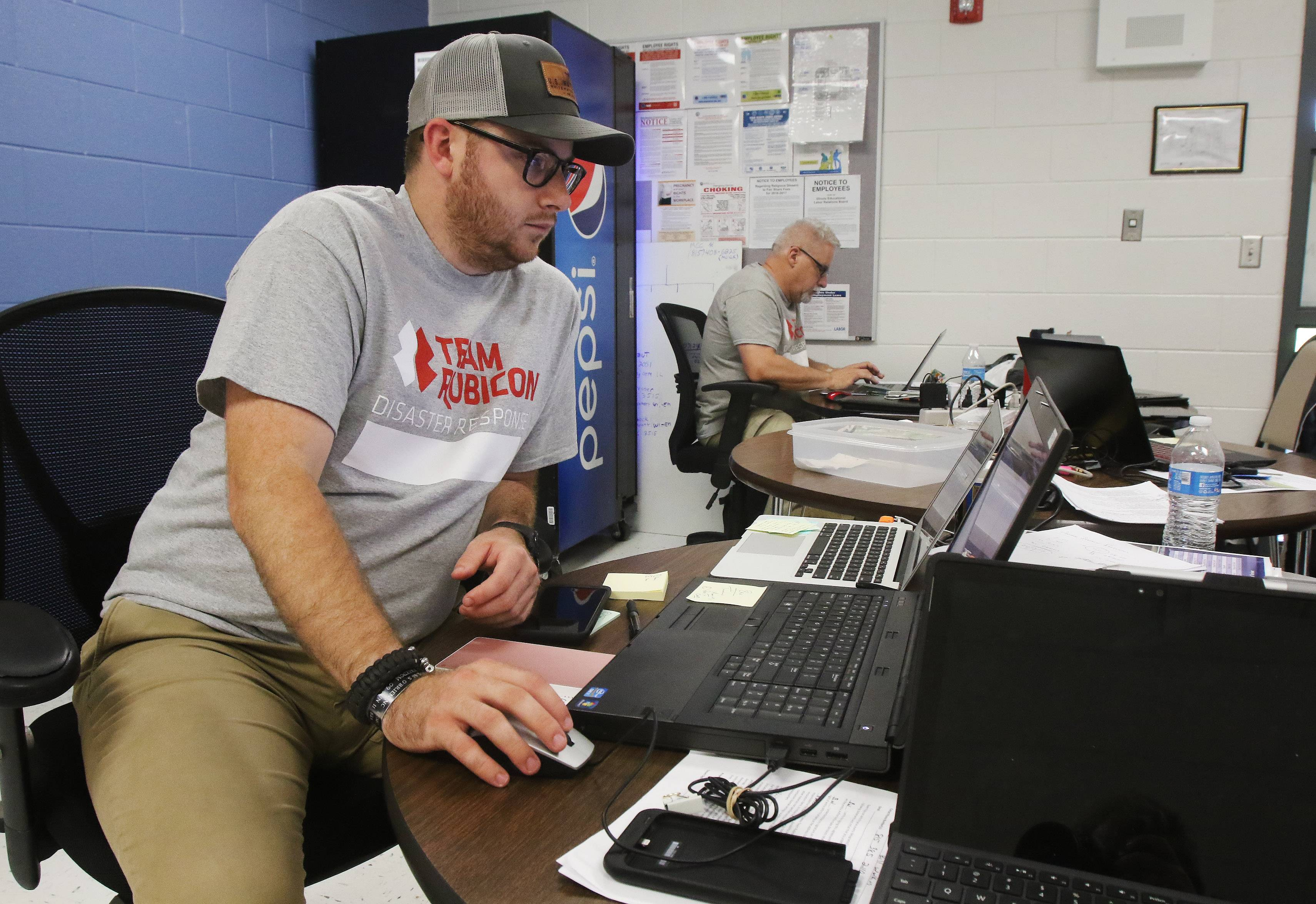 Firefighter Aaron Marshall of Atlanta works in the Team Rubicon command center at Johnsburg Junior High School on Tuesday as part of Operation Fox Yeah to help suburban residents who suffered losses in this month's record floods.
