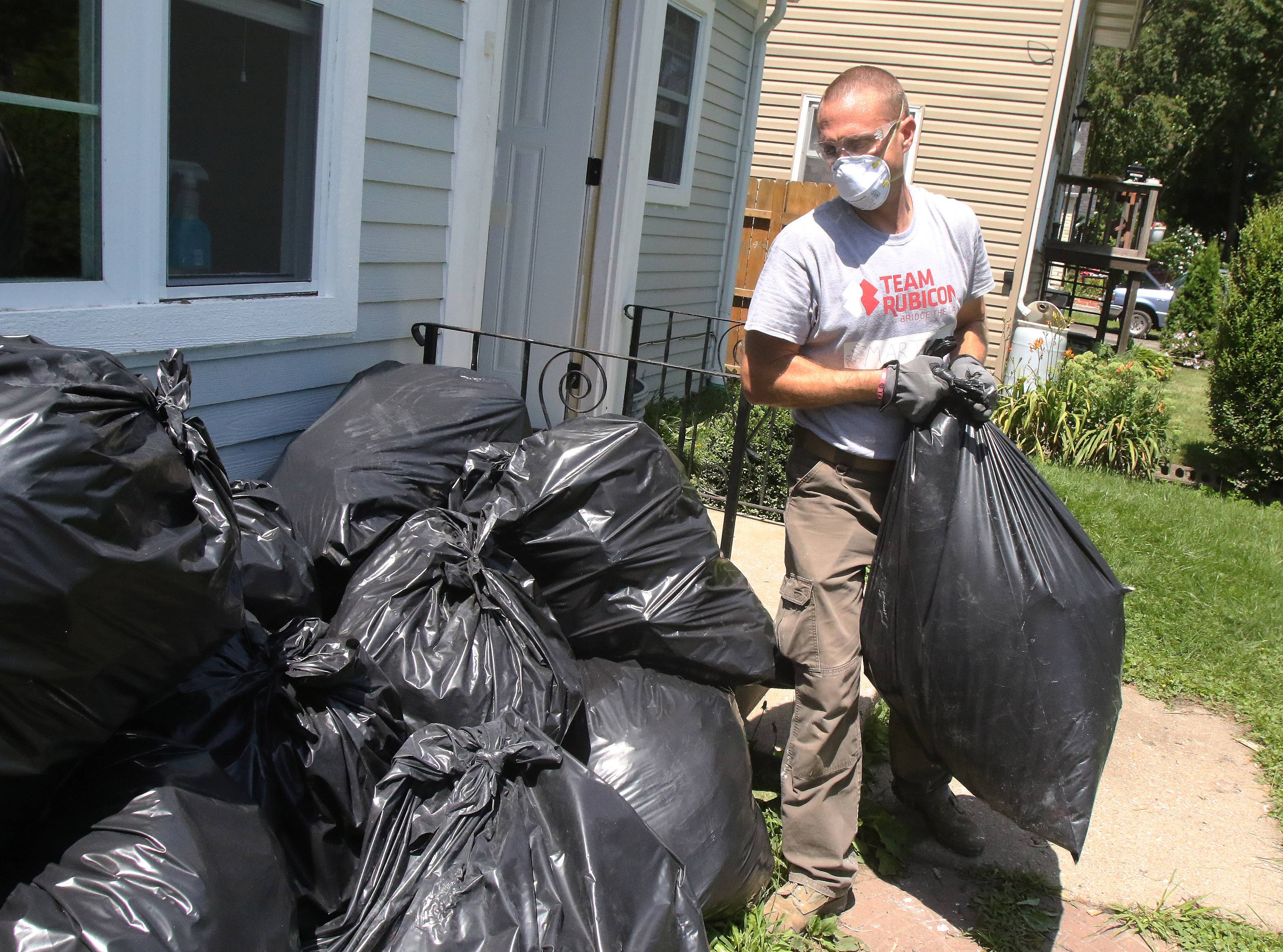 Veteran Adam Martin of Indianapolis stacks bags of damaged drywall outside as members of Team Rubicon repair a flood-damaged Round Lake Beach home Tuesday.
