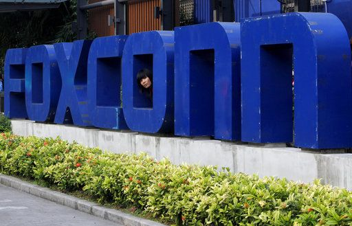 "FILE - In this May 27, 2010 file photo, a worker looks out through the logo at the entrance of the Foxconn complex in the southern Chinese city of Shenzhen. Wisconsin Gov. Scott Walker says President Donald Trump plans to make a ""major jobs announcement for Wisconsin"" as anticipation builds it will be about electronics giant Foxconn locating in the state. Taiwan-based Foxconn is best known as the assembler of the iPhone. Wisconsin is among seven states, mostly in the Midwest, that the company has named as possible locations to build the its first liquid-crystal display factory that could mean tens of thousands of jobs."