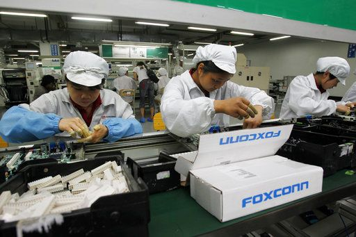 "FILE - In this May 26, 2010 file photo, staff members work on the production line at the Foxconn complex in the southern Chinese city of Shenzhen, southern China. Wisconsin Gov. Scott Walker says President Donald Trump plans to make a ""major jobs announcement for Wisconsin"" as anticipation builds it will be about electronics giant Foxconn locating in the state. Taiwan-based Foxconn is best known as the assembler of the iPhone. Wisconsin is among seven states, mostly in the Midwest, that the company has named as possible locations to build the its first liquid-crystal display factory that could mean tens of thousands of jobs."