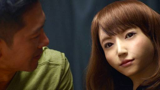 "Adam Yamaguchi, left, inspects a female life-like robot in Japan, in an investigative report for ""CBSN: On Assignment,"" a primetime summer series premiering Monday."