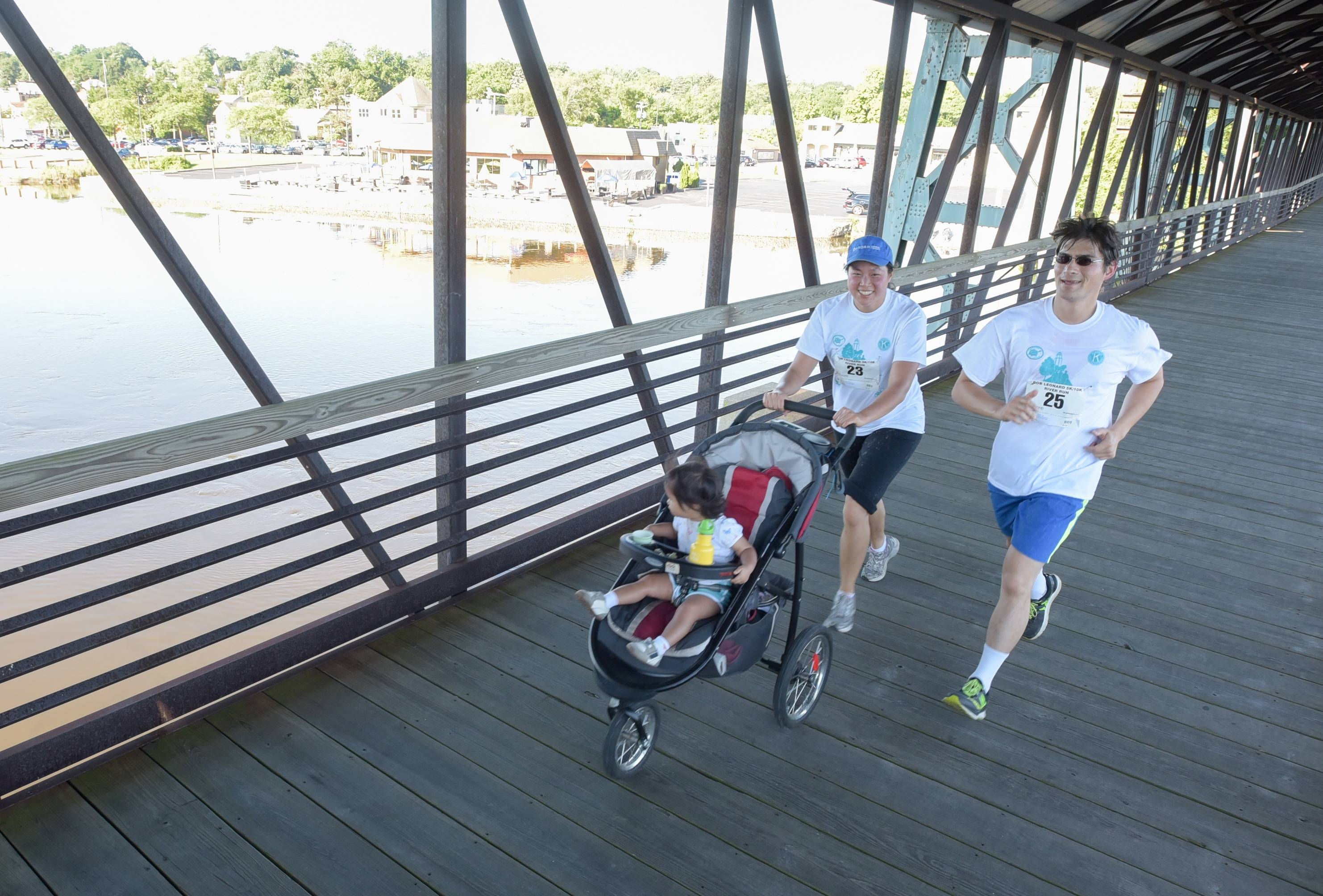 John Lang and Kim Hsu of St. Charles, along with daughter Katara Lang, participate in the Bob Leonard 5K/10K River Run at Pottawatomie Park in St. Charles Sunday.