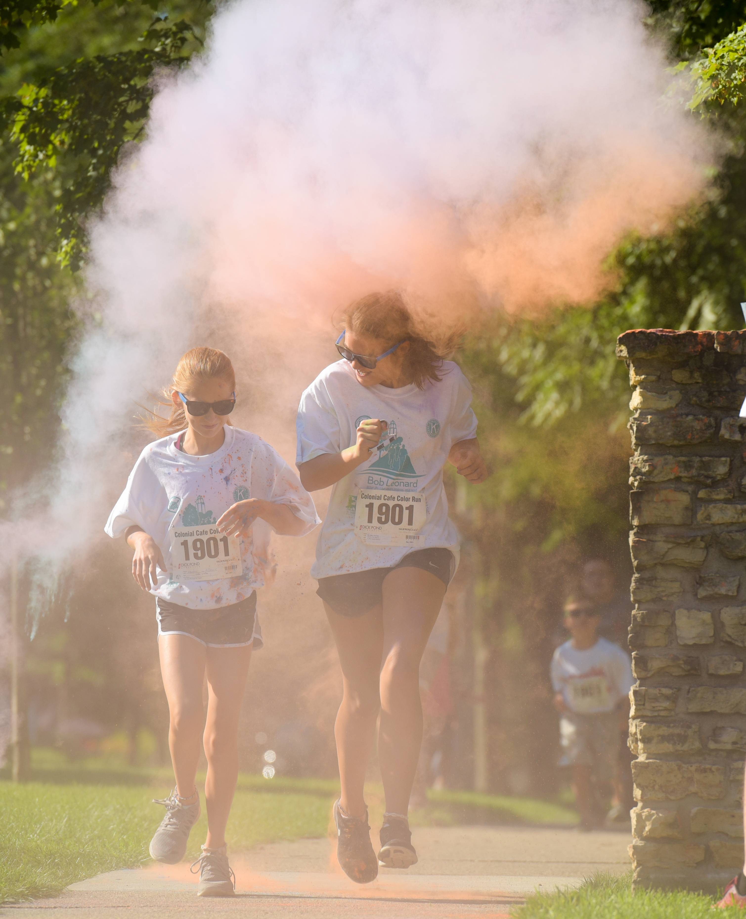 Runners in the Colonial Cafe Family 1K Color Run get doused with colored powder.
