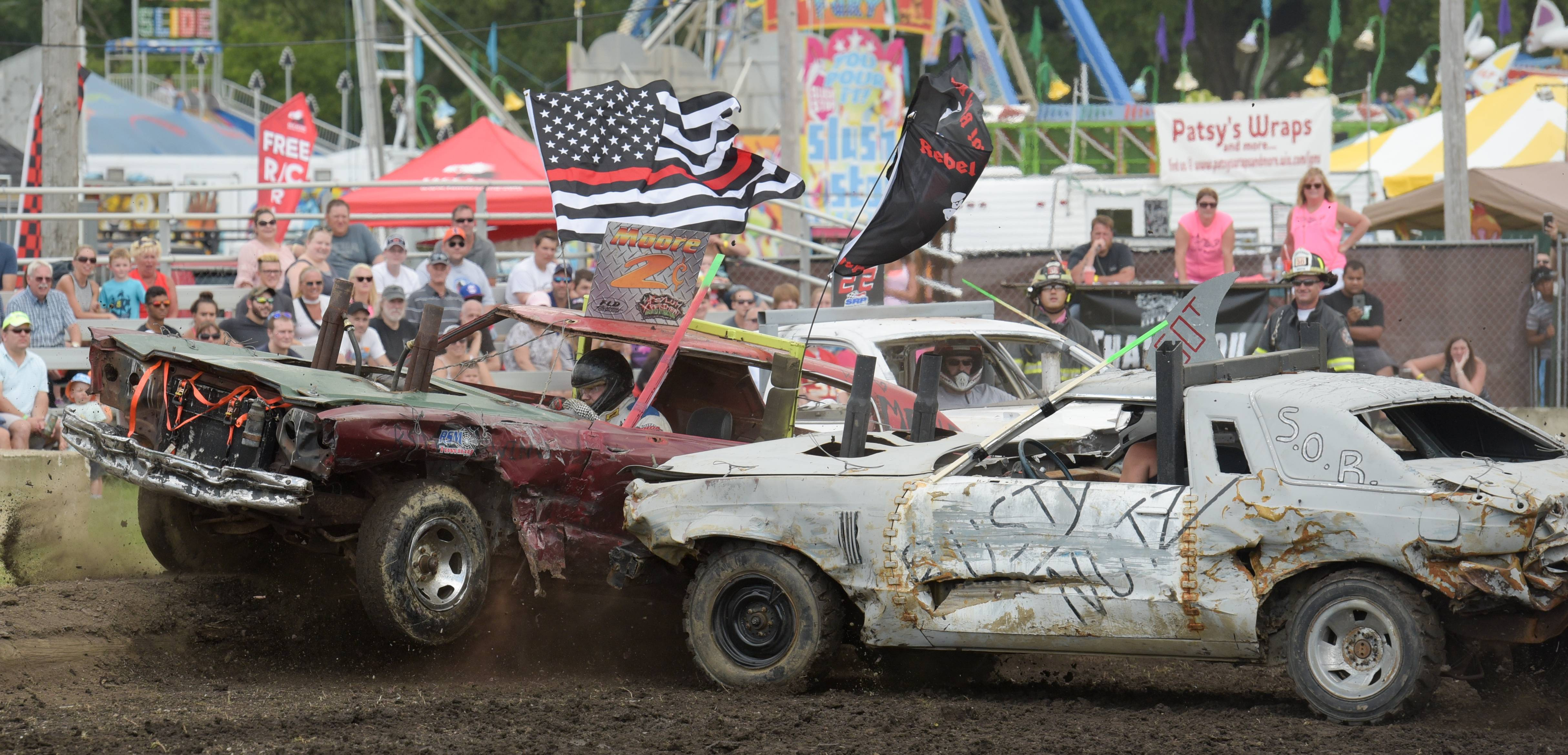 James Moore of Lombard takes a hit by Dan Green of Harvard during the demolition derby at the DuPage County Fair on Sunday. Moore drove one of two cars in the heat to move onto the finals.