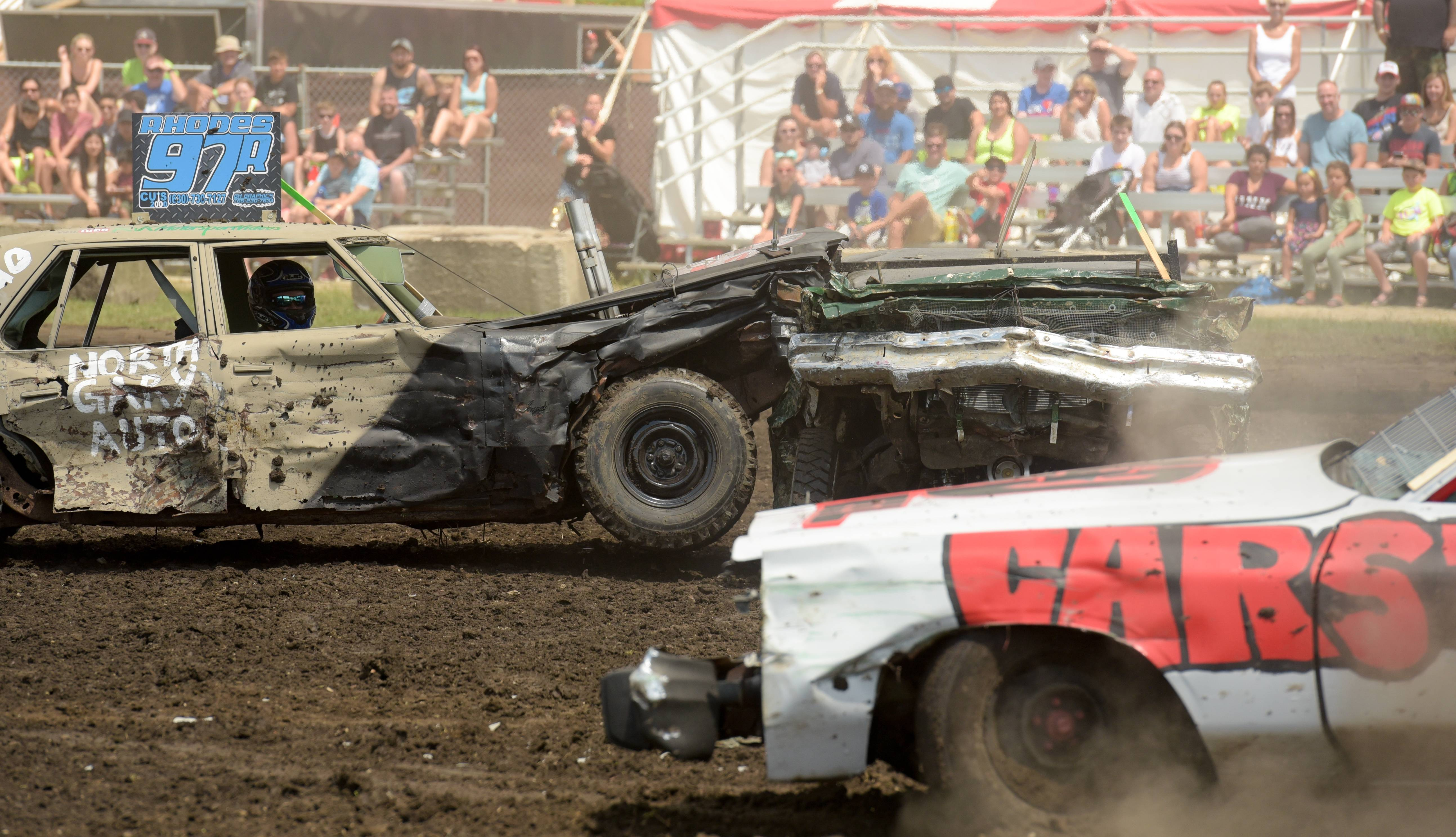 Adkin Rhodes of St. Charles inflicts some damage to Erik Johnson of Melrose Park during the demolition derby at the DuPage County Fair on Sunday. Rhodes survived the heat and moved on to the finals.