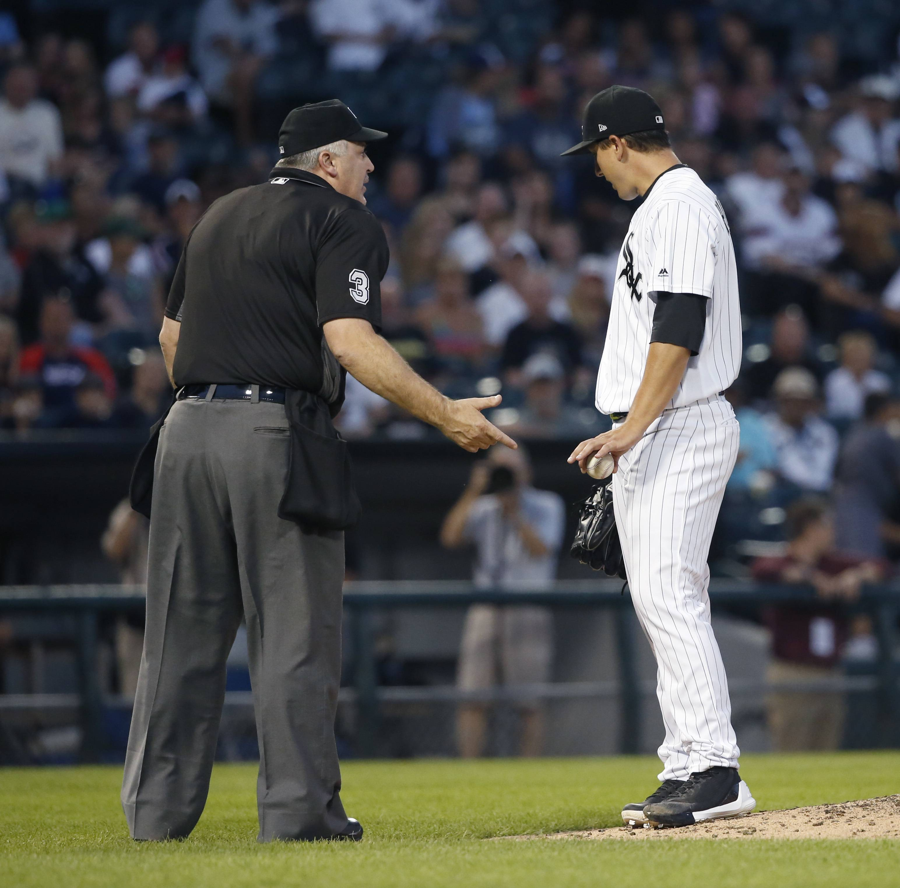 Home plate umpire Bill Welke, left, comes to the mound to talk with Chicago White Sox starting pitcher Derek Holland during the fourth inning of Chicago's baseball game against the Cleveland Indians on Friday, July 28, 2017, in Chicago. (AP Photo/Charles Rex Arbogast)