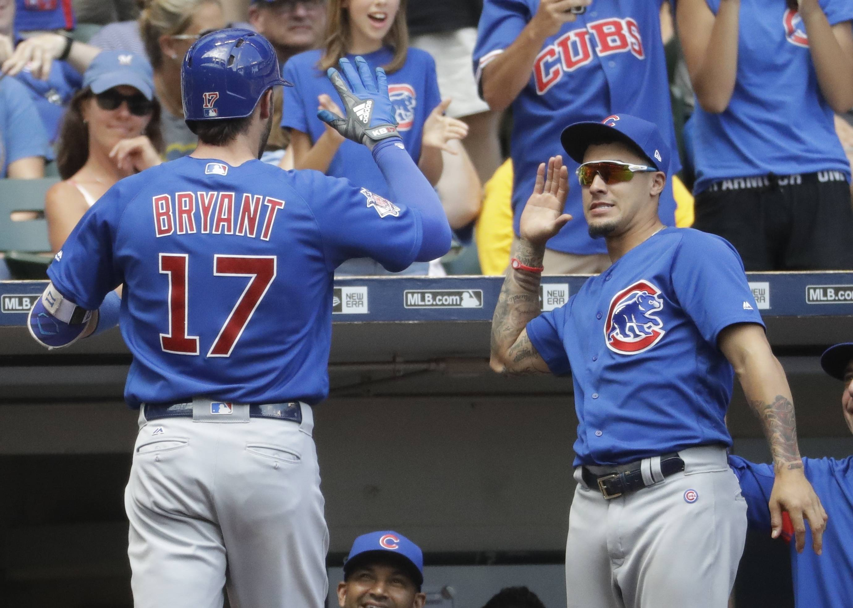 Chicago Cubs' Kris Bryant is congratulated by Javier Baez after hitting a home run during the eighth inning of a baseball game against the Milwaukee Brewers Sunday, July 30, 2017, in Milwaukee.