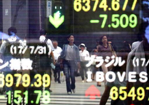 People are reflected on an electronic stock indicator of a securities firm in Tokyo, Monday, July 31, 2017. Shares were mixed in Asia early Monday, with Chinese markets shrugging off weaker factory output indicators while Japan's Nikkei index sagged thanks to a surge in the value of the yen. (AP Photo/Shizuo Kambayashi)