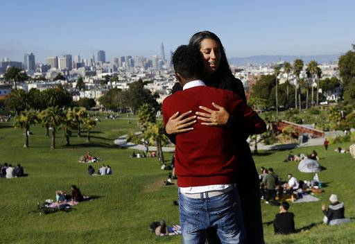 In this July 14, 2017 photo, Julie Rajagopal, facing, hugs her 16-year-old foster child from Eritrea after posing for photos at Dolores Park in San Francisco. When he landed in March, he was among the last refugee foster children to make it into the U.S. Trump administration travel bans declared to block terrorists also are halting a small, three-decade-old program bringing orphan refugee children to waiting foster families in the United States. (AP Photo/Jeff Chiu)