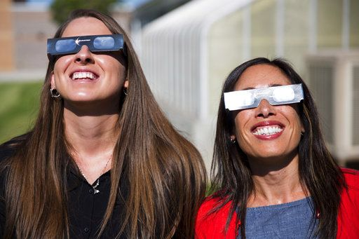 ADVANCE FOR RELEASE SATURDAY, JULY 29, 2017, AT 12:01 A.M. MDT. AND THEREAFTER In this Tuesday, July 18, 2017 photo, Twin Falls High School science teachers Ashley Moretti, left, and Candace Wright, right, use their eclipse shades to look at the sun as they pose for a portrait at Twin Falls High School in Twin Falls, Idaho. The district bought 11,000 pairs of solar glasses, enough for every student and staff member to view the solar eclipse Aug. 21, from Twin Falls.  (Pat Sutphin/The Times-News via AP)