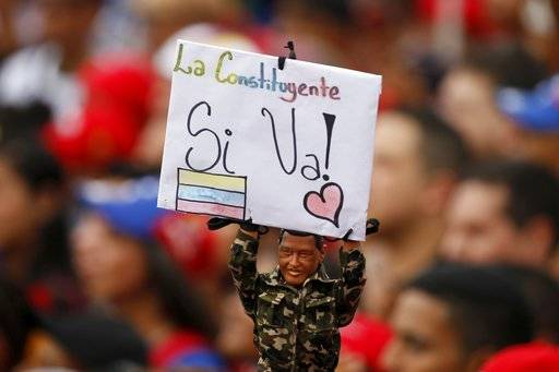 "A supporter of Venezuela's President Nicolas Maduro holds a doll of the late President Hugo Chavez holding a sign that reads in Spanish ""Constituent Assembly, Yes it's going"" during a political rally with Venezuela's President Nicolas Maduro, in Caracas, Venezuela, Thursday, July 27, 2017. President Maduro has provoked international outcry and enraged an opposition demanding his resignation with his push to elect an assembly that will rewrite the troubled South American nation's constitution. Sunday's election will cap nearly four months of political upheaval that has left thousands detained and injured and at least 100 dead. (AP Photo/Ariana Cubillos)"