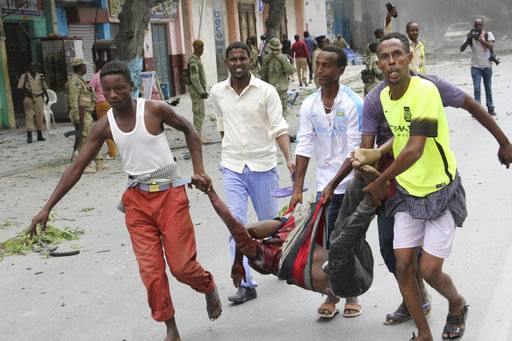 Somalis carry away a wounded civilian who was injured in a suicide car bomb attack on a popular mall in Mogadishu, Somalia, Sunday, July 30, 2017. A police officer says a car bomb blast near a police station in Somalia's capital has killed at least five people and wounded at least 13 others. Most of the victims are civilians. The Somalia-based extremist group al-Shabab often carries out deadly bombings in Mogadishu. (AP Photo/Farah Abdi Warsameh)