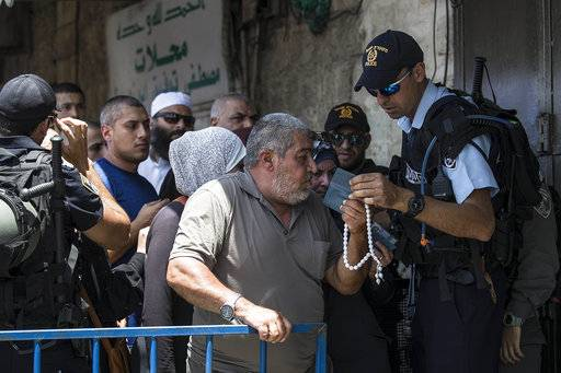 FILE - In this Friday, July 28, 2017, file photo an Israeli police officer checks the ID of a Palestinian man at a checkpoint outside Jerusalem's Old City. The latest crisis over one of the most combustible spots in the Middle East has been defused, but has pushed the leaders of Israel, Jordan and the Palestinians into taking more uncompromising positions that could easily trigger new tensions. (AP Photo/Tsafrir Abayov, File)