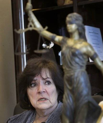 "In this Wednesday, March 15, 2017 photo, Oakland County Prosecuting Attorney Jessica Cooper speaks during an interview in her office next to her statue of ""Lady Justice"" in Pontiac, Mich. Cooper argues that all her juvenile lifer cases are rare since they comprise just a small portion of all the criminal cases her office has handled over many years. She is seeking new natural life sentences in 44 of 49 of the county's juvenile lifer cases."