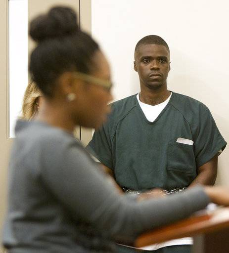 "In this Friday, Sept. 30, 2016 photo, Ahmad Williams listens as Danneka Cooper, the sister of Derrick Pimpleton, gives a victim's statement during Williams' resentencing hearing at the Kent County Courthouse in Grand Rapids, Mich. Cooper testified that 18 years wasn't enough time to make up for her family's loss. ""He broke my mother's heart,"" she said. Williams, who was 15 at the time of the killing, apologized. His new sentence makes him eligible for parole in 2024. (Cory Morse/The Grand Rapids Press via AP)"