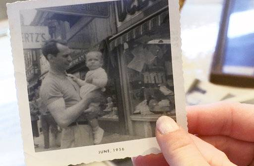"In this Wednesday, June 7, 2017 image made from video, Denyse DeLuca holds a photo of her grandfather, Eugene DeLuca, with his son, Joe. In 1977, the store owner was fatally shot by 17-year-old Joseph Evans during a robbery. Years after the photo was taken, Joe dropped out of college to help open a new store, but his father's death forced the closing of both. DeLuca's widow began drinking heavily and spent the rest of her life as an alcoholic. Denyse says, ""My father lost his dad and then he basically lost his mother."" (AP Photo/Mike Householder)"