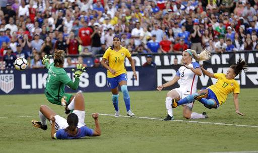 United States defender Julie Ertz (8) scores a goal past Brazil goalkeeper Barbara, left, as Brazil defender Adnressinha (17) defends during the second half of a Tournament of Nations women's soccer match Sunday, July 30, 2017, in San Diego. The United States won, 4-3. (AP Photo/Gregory Bull)