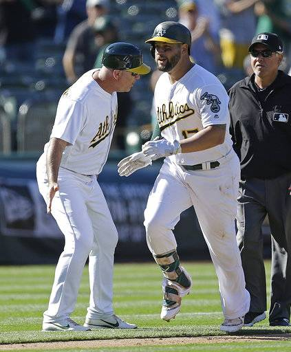 Oakland Athletics' Yonder Alonso, right, is congratulated by third base coach Steve Scarsone after hitting a winning home run in the 12th inning of a baseball game against the Minnesota Twins, Sunday, July 30, 2017, in Oakland, Calif. (AP Photo/Ben Margot)