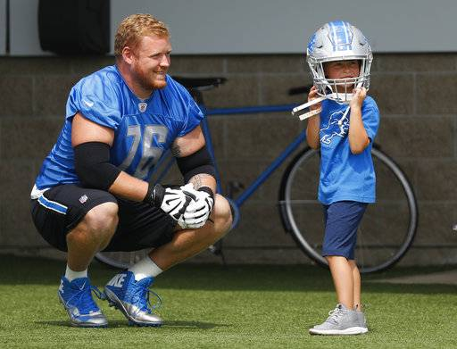 Detroit Lions offensive guard T.J. Lang watches his son J.J., 5, try on his helmet before NFL football training camp in Allen Park, Mich., Sunday, July 30, 2017. (AP Photo/Paul Sancya)