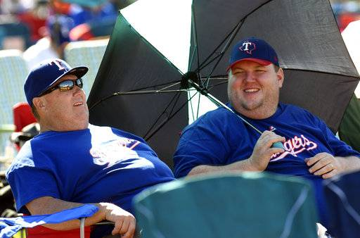 Dean Kuykenell ,left, and his son Jake Kuykenell both of Burleson, Texas wait for the start of the National Baseball Hall of Fame induction ceremony to see Ivan Rodriguez, inducted at the Clark Sports Center on Sunday, July 30, 2017, in Cooperstown, N.Y. (AP Photo/Hans Pennink)