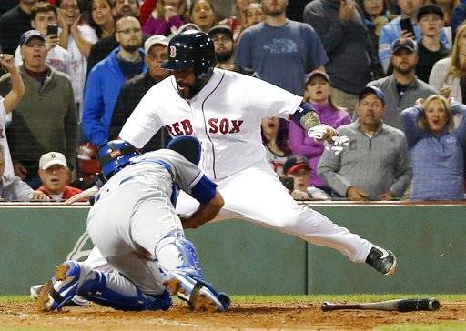 Boston Red Sox's Sandy Leon scores behind Kansas City Royals' Drew Butera on a ground-out by Eduardo Nunez during the 10th inning of a baseball game in Boston, Saturday, July 29, 2017. The Red Sox won 9-8. (AP Photo/Michael Dwyer)