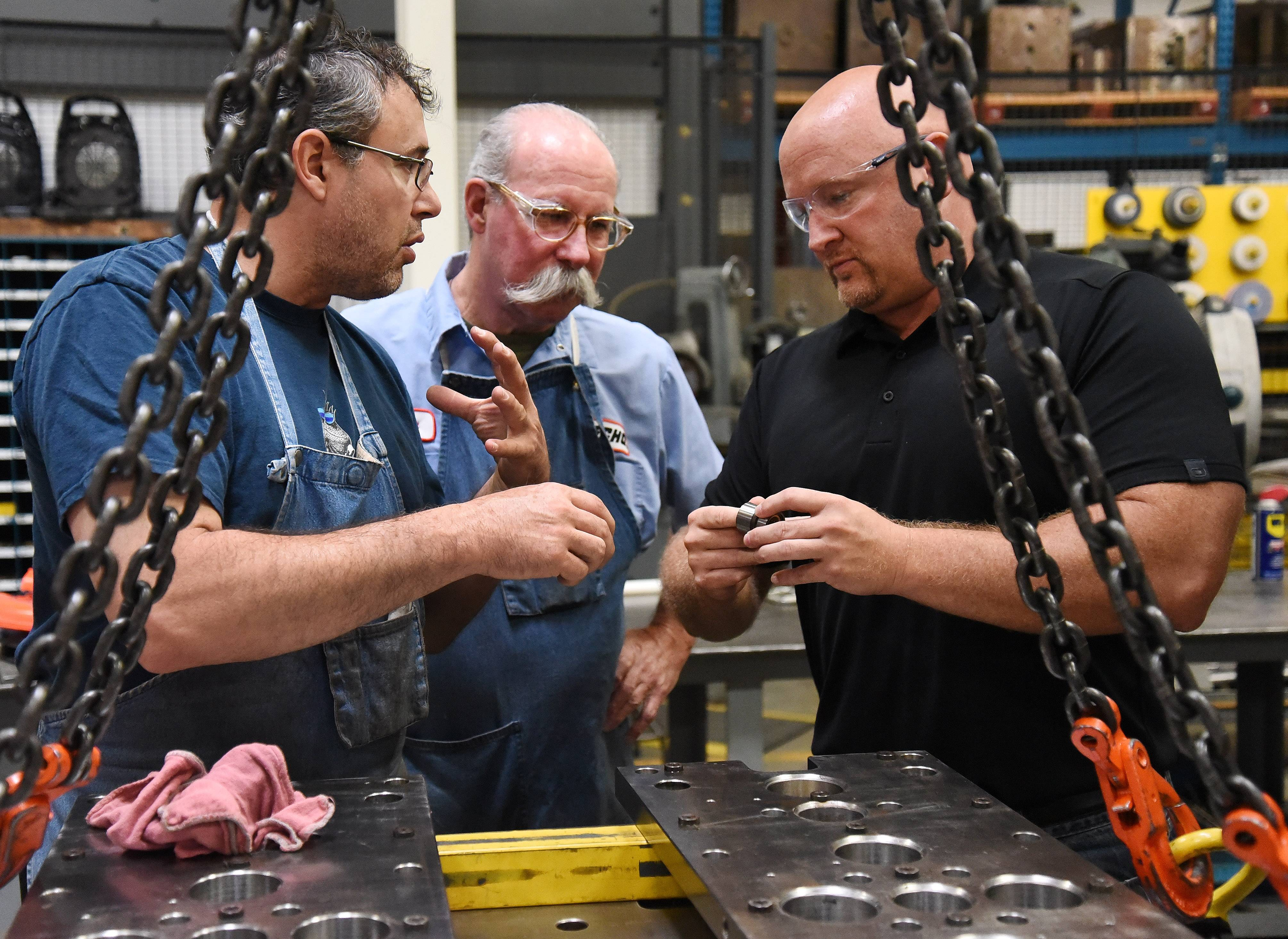 Mold makers Jeff Gorden, from left, and William Ross go over some preventive maintenance on injection mold tooling with Ryan Ladley, senior director of operations at Echo Inc. in Lake Zurich.
