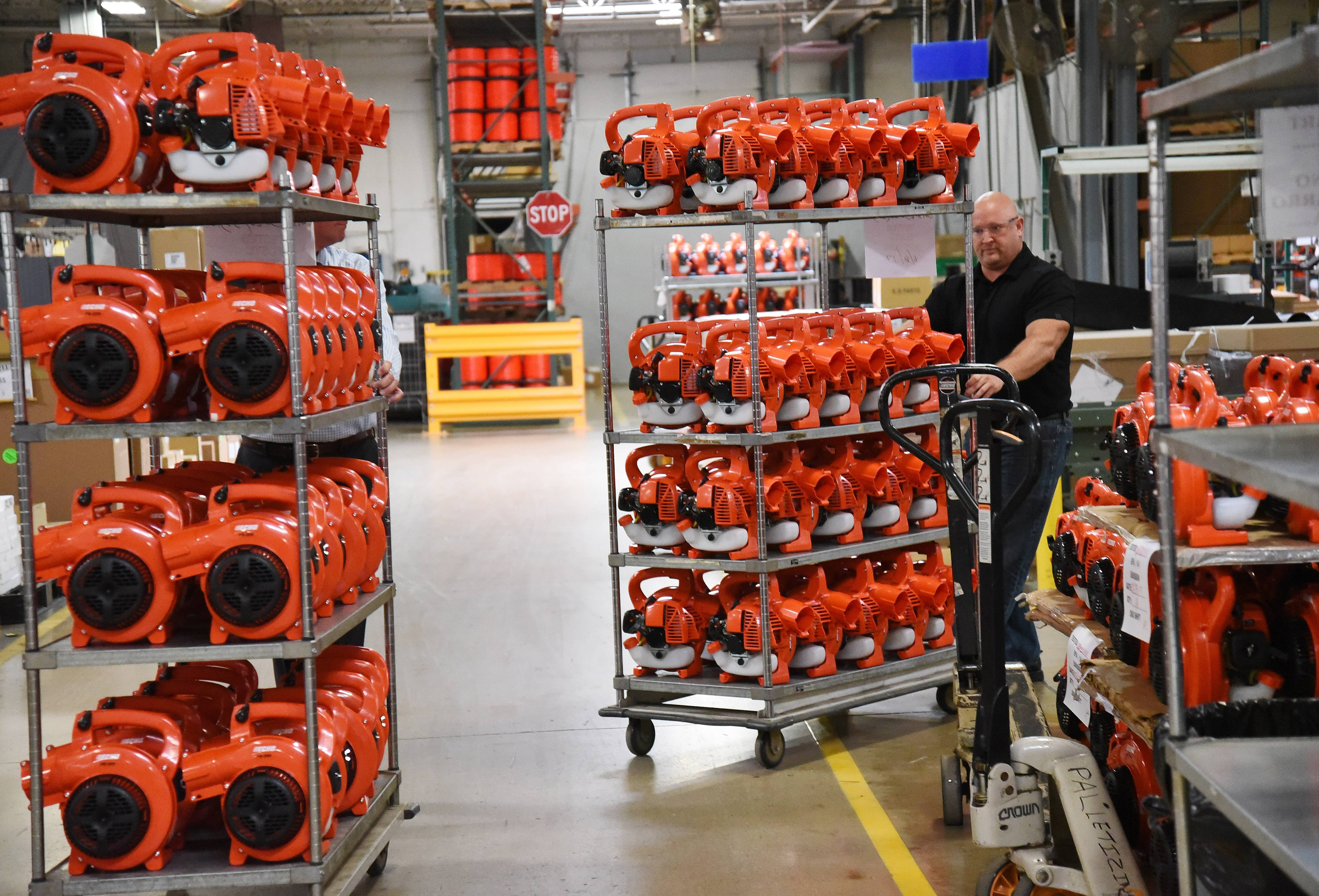 Echo Inc. President Tim Dorsey, left, and Ryan Ladley, senior director of operations, move racks of leaf blowers at Echo Inc., in Lake Zurich.