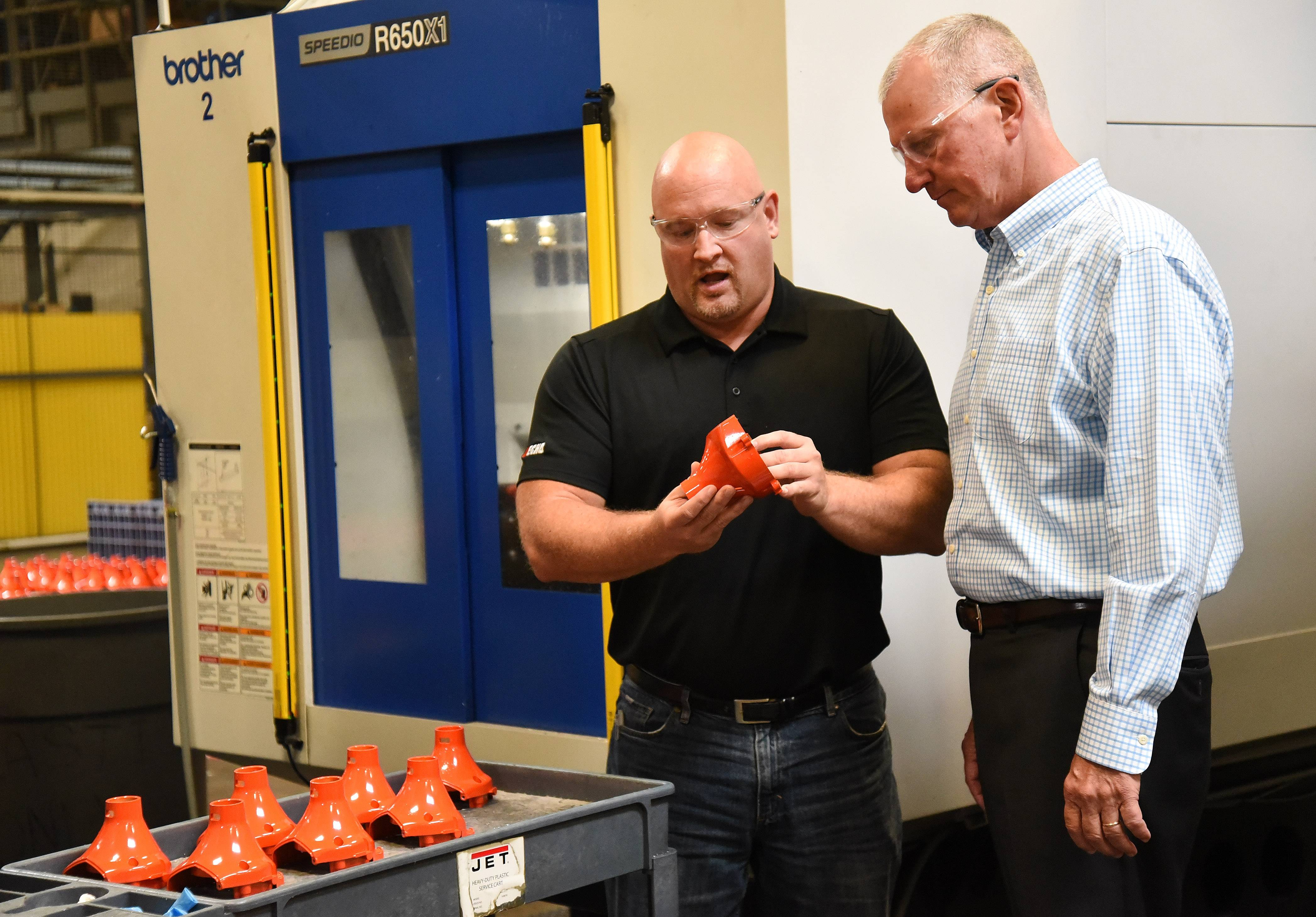 Ryan Ladley, senior director of operations and Tim Dorsey, company president, inspect band covers for trimmers at Echo Inc. in Lake Zurich.