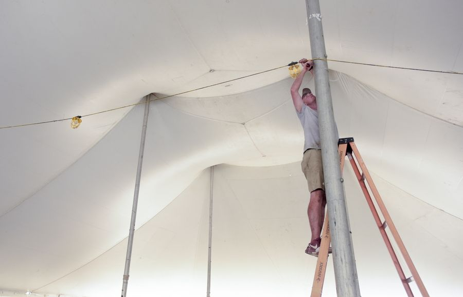 Eric Bottelsen of Braun Events in Schaumburg removes the lighting from a tent Monday as crews clean up after the DuPage County Fair.
