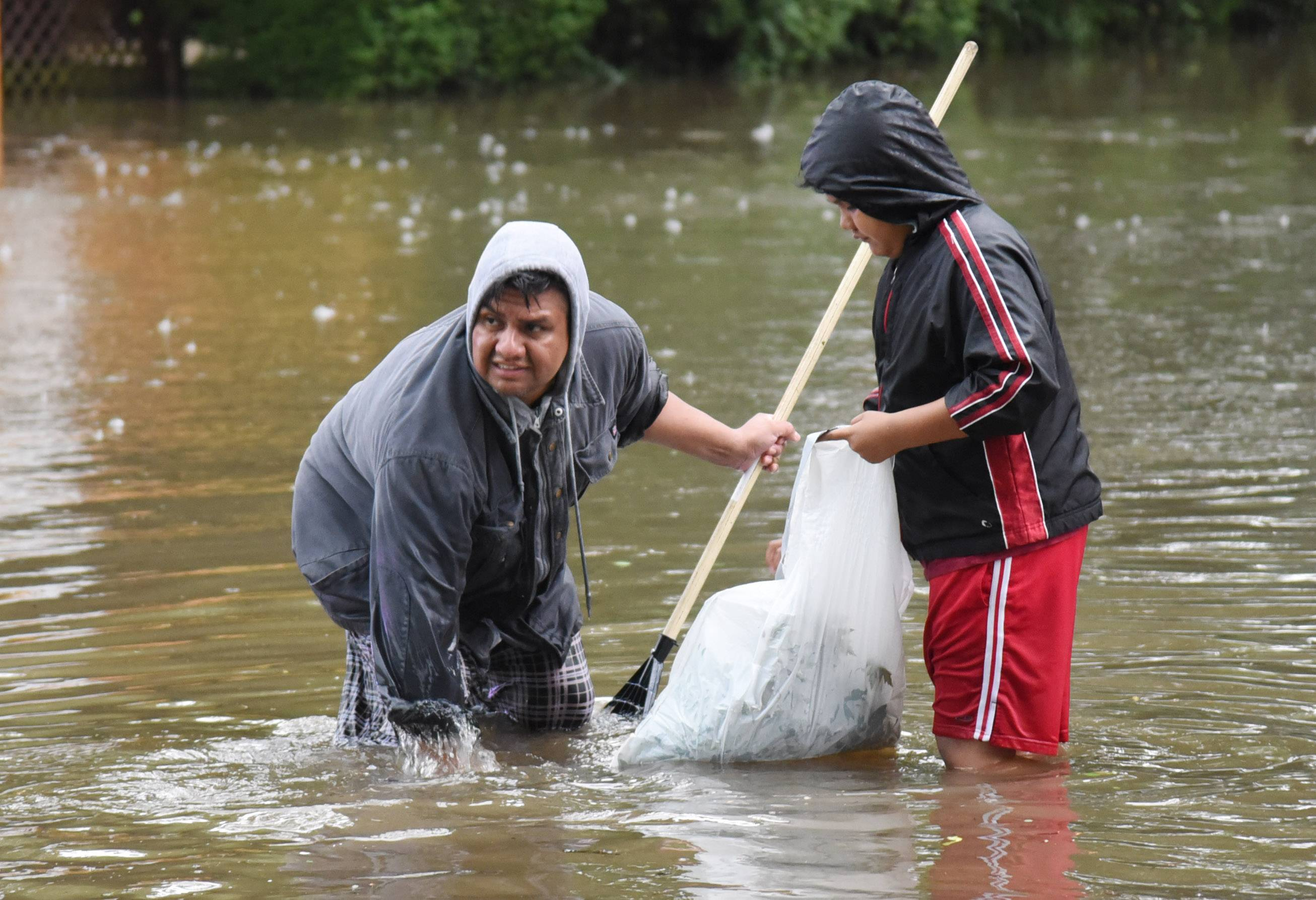Jorge Morales and his 10-year-old son Ariel try to clear drains in front of his house on Lincoln Avenue and West Division Street in Mundelein during the recent flooding.