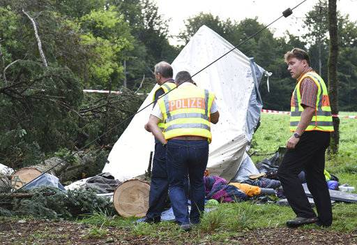 Police stands next to a destroyed tent in Rickenbach Germany Wednesday Aug.  sc 1 st  Daily Herald & Storm in Germany kills 1 boy hurts 4 as tree falls on tent