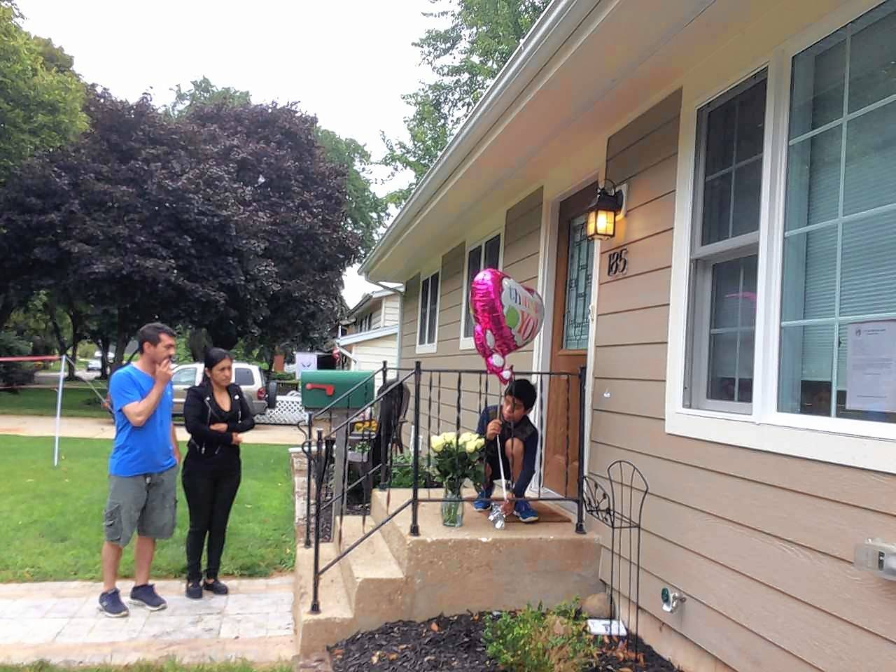 Neighbors, from left, Juan Viveros, Maribel Hernandez watch Juan Viveros Jr., place a balloon on the porch of the home where a 31-year-old woman and a 15-year-old girl were shot and killed Thursday.