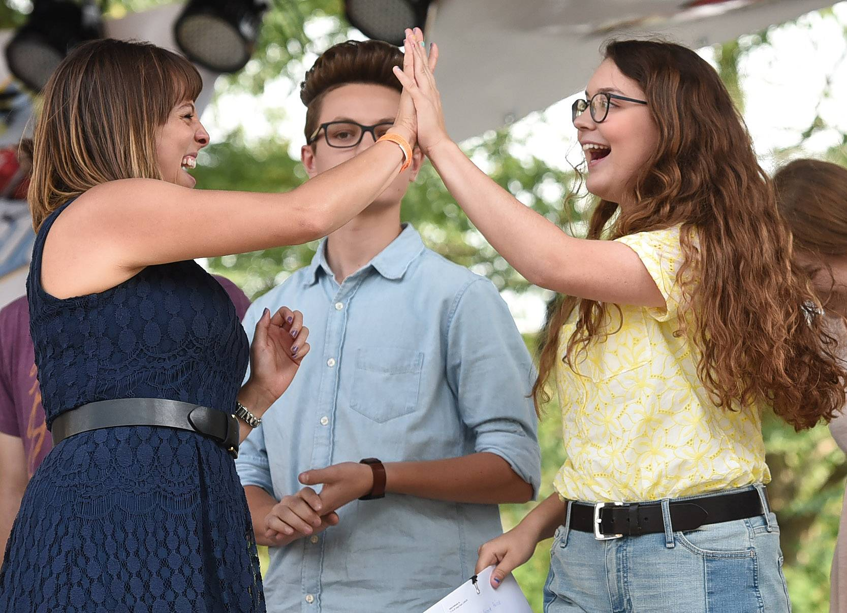 Kayla Seeber of Poplar Grove, right, is congratulated by Cassandra Henwood of Elgin after being named Fan Favorite at the 2017 Suburban Chicago's Got Talent finale on Saturday at the Taste of Arlington Heights. Looking on is Belvidere singer-songwriter Adem Dalipi.