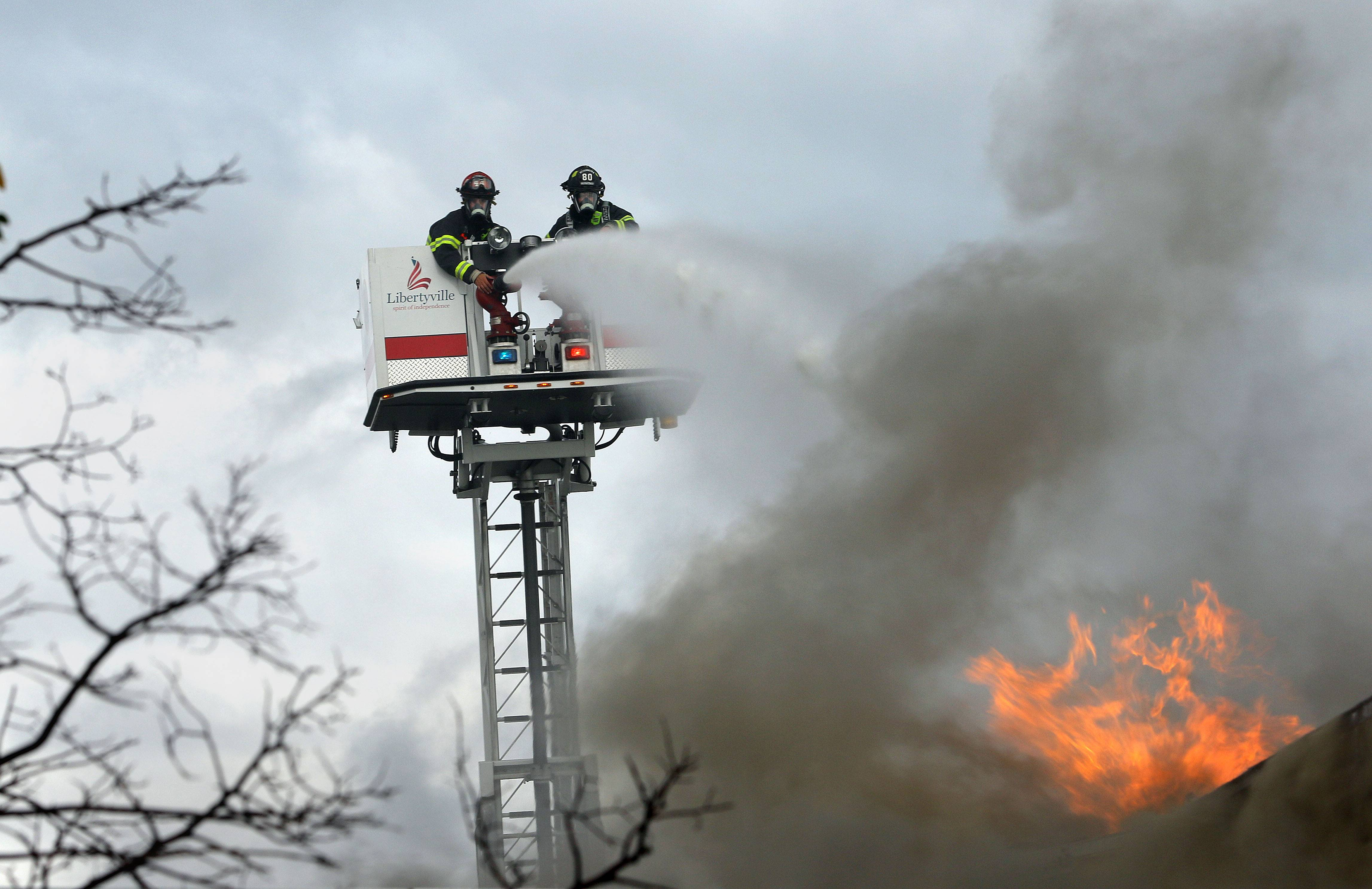 Libertyville firefighters work from a ladder truck during a multiple alarm fire at Campos Income Tax in Round Lake Friday.