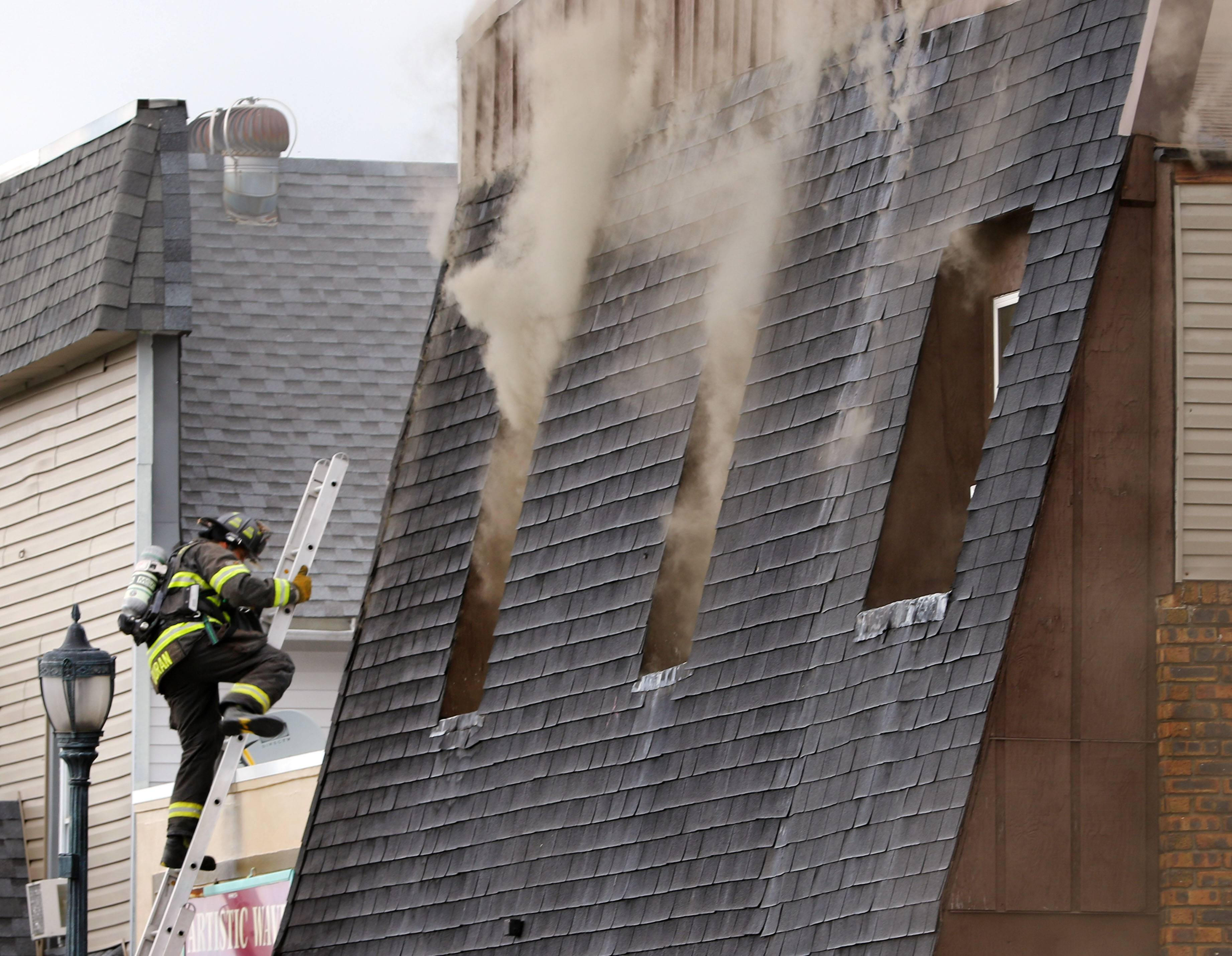 A firefighter climbs to the roof during a multiple alarm fire Friday at an apartment building in downtown Round Lake. A 33-year-old man killed in the fire was identified Monday.