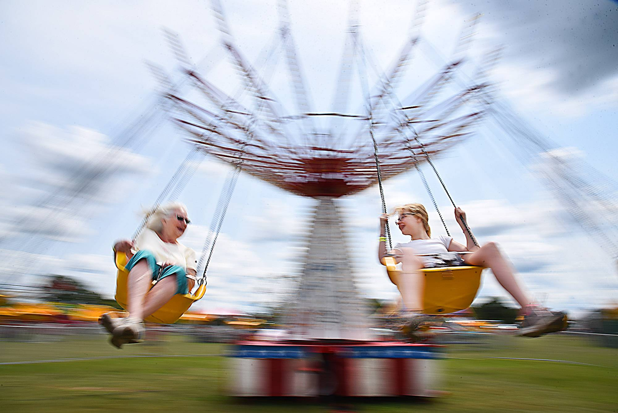 Ellie Marchialette, 12, looks at the her grandmother Karen Jones of Hampshire as the pair spin on the Musical Chairs ride Saturday at the Coon Creek Country Days festival in Hampshire.