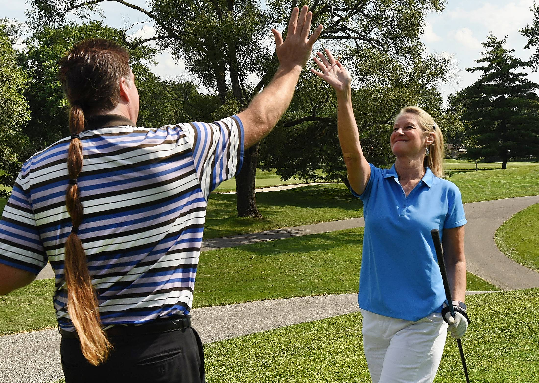 David Thorburn of Schaumburg congratulates Kathy Thomas of Chicago on her opening tee shot Wednesday at the 10th Annual Links Technology Cup golf outing benefiting the Schaumburg Park Foundation.