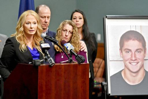 FILE – In this May 5, 2017, file photo, Centre County, Pa., District Attorney Stacy Parks Miller, left, announces the findings of an investigation into the death of Penn State University fraternity pledge Tim Piazza, seen in photo at right, as his parents, Jim and Evelyn Piazza, second and third from left, stand nearby during a news conference in Bellefonte, Pa. A preliminary hearing is set to resume Thursday, Aug. 10 for members of Penn State University's now-shuttered Beta Theta Pi fraternity chapter, accused in the Feb. 4 death of 19-year-old Tim Piazza, of Lebanon, N.J., after a night of heavy drinking. (Abby Drey /Centre Daily Times via AP, File)