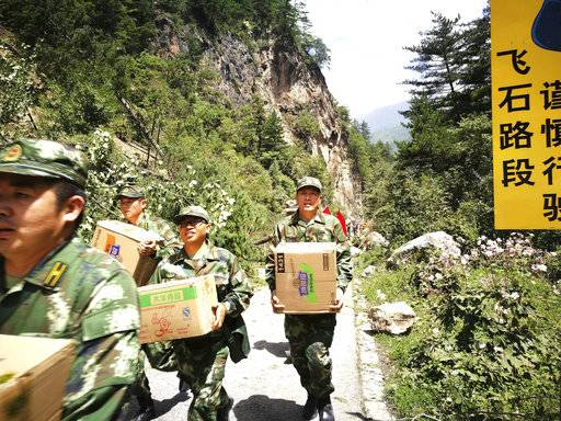Paramilitary policemen carry boxes of supplies past a section of road blocked by a landslide after an earthquake in Jiuzhaigou county in southwestern China's Sichuan province, Wednesday, Aug. 9, 2017. Stranded tourists and residents struggled Wednesday to clear roads and cope with power cuts caused by a powerful earthquake that killed several people and injured hundreds more. (Chinatopix via AP)
