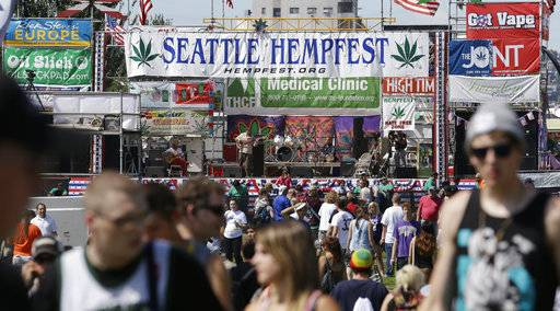 FILE--In this Aug. 16, 2013, file photo, people walk past the main stage at the first day of Hempfest, Friday, Aug. 16, 2013, in Seattle. Seattle on Tuesday, Aug. 8, 2017, agreed to drop a $1,000 fine issued to the nonprofit organization that runs HempFest--the annual summer marijuana celebration. The city accused the organization of operating a marijuana business without a license but later said it had no evidence the group violated the law. (AP Photo/Elaine Thompson, file)