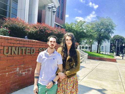 This Aug. 4, 2017, photo provided by Jillian Weiss shows Dane Lane, left, and his transgender wife, Allegra Schawe-Lane, outside the federal courthouse in Covington, Ky. The couple is filing a lawsuit against Amazon, alleging that they endured sustained discrimination and harassment during a year as co-workers at an Amazon warehouse in Kentucky. (Jillian Weiss via AP)