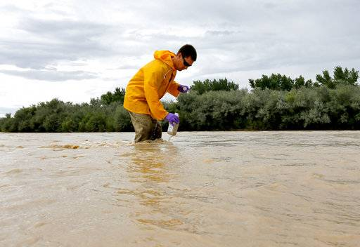 FILE - In this Aug. 11, 2015, file photo, hydrologic technician Ryan Parker gathers water samples from the San Juan River, in Montezuma Creek, Utah. Utah has filed a claim for $1.9 billion from the U.S. Environmental Protection Agency, saying a mine wastewater spill in Colorado triggered by the EPA damaged the San Juan and other waterways in Utah, as well as causing damage to soil and wildlife. (AP Photo/Matt York, File)