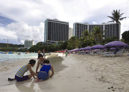 "A family plays in the sand in Tumon, Guam on Thursday, Aug. 10, 2017. The small U.S. territory of Guam has become a focal point after North Korea's army threatened to use ballistic missiles to create an ""enveloping fire"" around the island. The exclamation came after President Donald Trump warned Pyongyang of ""fire and fury like the world has never seen."" (AP Photo/Tassanee Vejpongsa)"