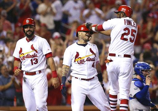St. Louis Cardinals' Yadier Molina is congratulated by Dexter Fowler after hitting a grand slam against the Kansas City Royals during the sixth inning of a baseball game Wednesday, Aug. 9, 2017, at Busch Stadium in St. Louis. At left is Matt Carpenter, who also scored on the home run. (Chris Lee/St. Louis Post-Dispatch via AP)
