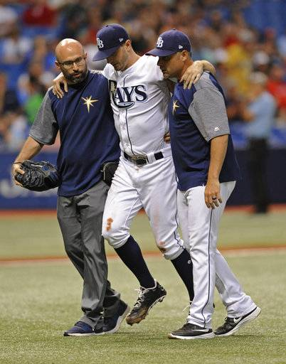 A Tampa Bay Rays trainer and manager Kevin Cash, right, help pitcher Jake Odorizzi, center, off the field after he was hit by a line drive on his right leg from Boston Red Sox's Eduardo Nunez during the fifth inning of a baseball game Wednesday, Aug. 9, 2017, in St. Petersburg, Fla. (AP Photo/Steve Nesius)
