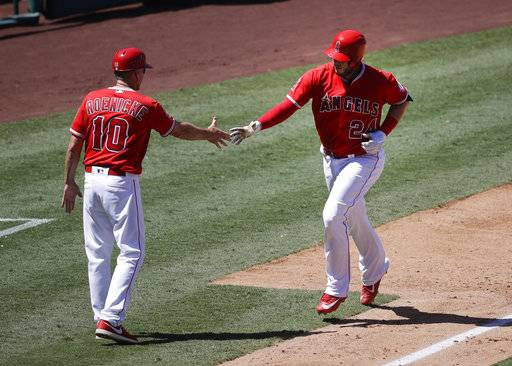 Los Angeles Angels' C.J. Cron, right, celebrates his two-run home run with third base coach Ron Roenicke during the sixth inning of a baseball game against the Baltimore Orioles, Wednesday, Aug. 9, 2017, in Anaheim, Calif. (AP Photo/Jae C. Hong)