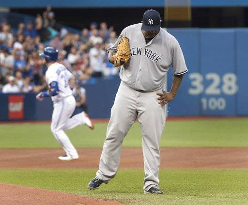 New York Yankees starting pitcher CC Sabathia walks off the mound after giving up a two run homerun to Toronto Blue Jays' Josh Donaldson circling the bases behind him in the first inning of their baseball game in Toronto on Tuesday, Aug. 8, 2017. (Fred Thornhill/The Canadian Press via AP)