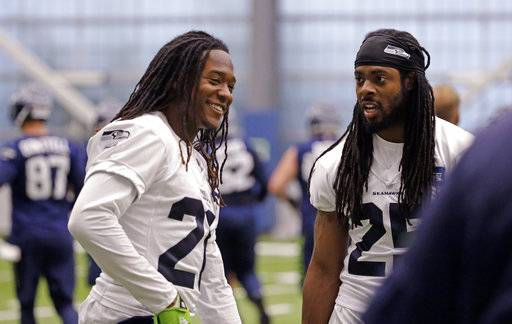 FILE - In this June 15, 2017, file photo, Seattle Seahawks' Shaquill Griffin, and Richard Sherman talk between drills at NFL football practice in Renton, Wash. Even though he's now a professional, Griffin is still in school. And in this case, Sherman is the teacher. It's part of the Seattle Seahawks examination of Griffin and how soon the rookie could step in as the cornerback opposite Sherman. (AP Photo/Elaine Thompson, File)