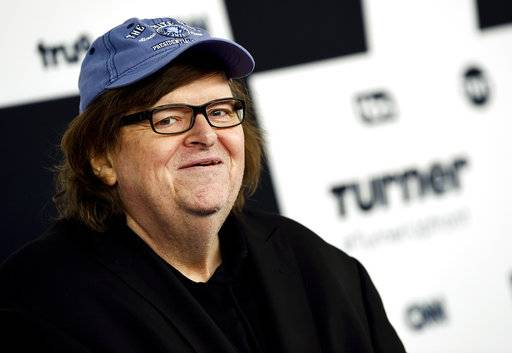 "FILE - In this May 17, 2017 file photo, filmmaker Michael Moore attends the Turner Network 2017 Upfront presentation at The Theater at Madison Square Garden in New York. Moore showed his patriotism by marching down the Avenue of the Americas with a drum and fife corps after making his Broadway debut. ""I say this to the people who disagree with me, we're all Americans. We're all in the same boat, and we're going to sink or swim together. I prefer not to sink. So let's find a way, if we can, to work together to save this country,� Moore said Thursday, Aug. 10. .(Photo by Evan Agostini/Invision/AP, File)"