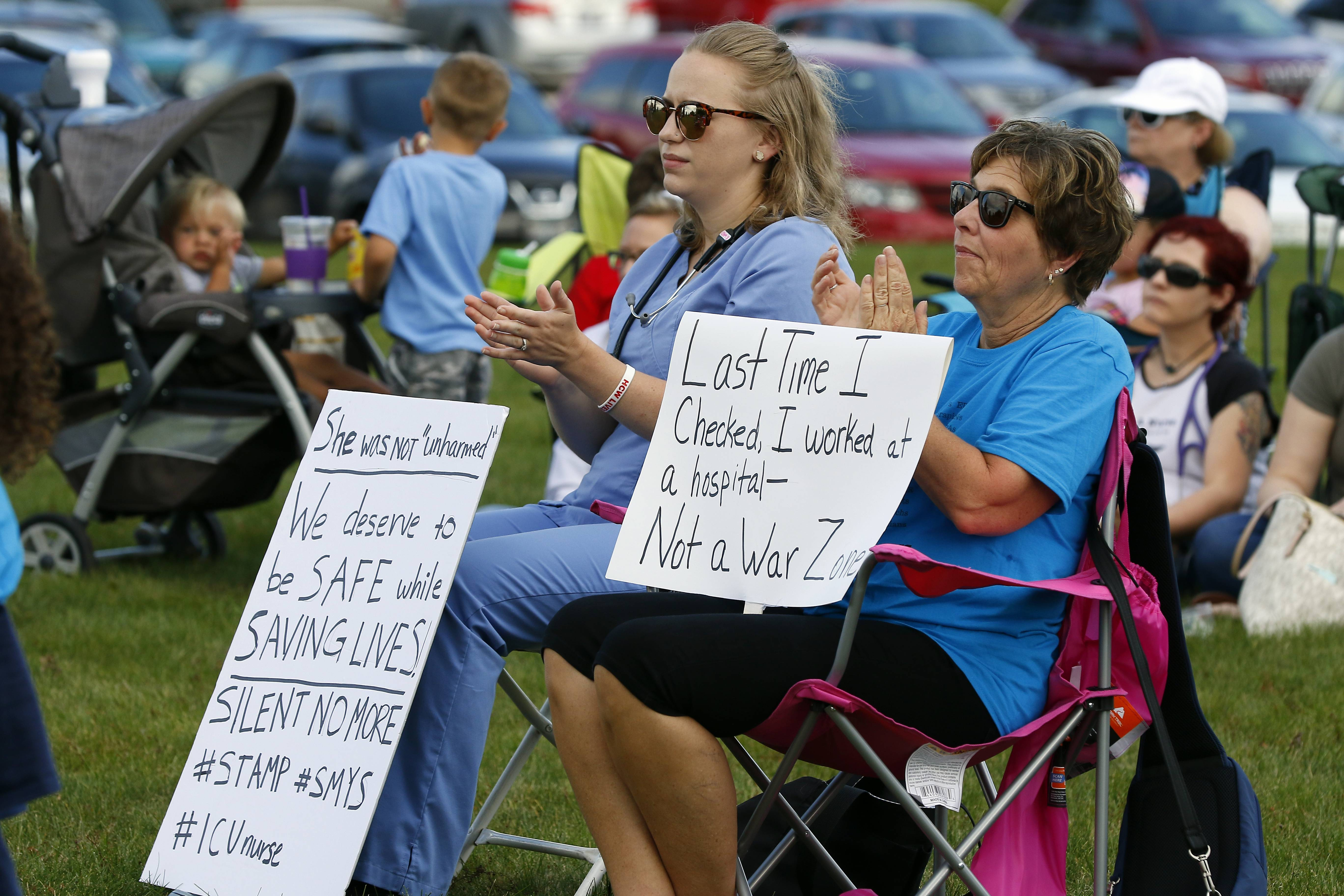 Katy Ward of Aurora, left, and Kim Bourdages of Dekalb use signs to display their feelings about the workplace safety of medical personnel during a rally Friday at the Kane County Judicial Center in St. Charles.